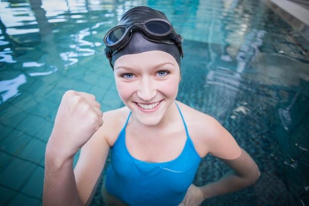 Caber mulher vestindo boné de nadar e óculos com o punho levantado na piscina