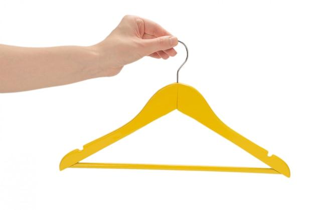 Cabide amarelo em fundo isolado de mão de mulher