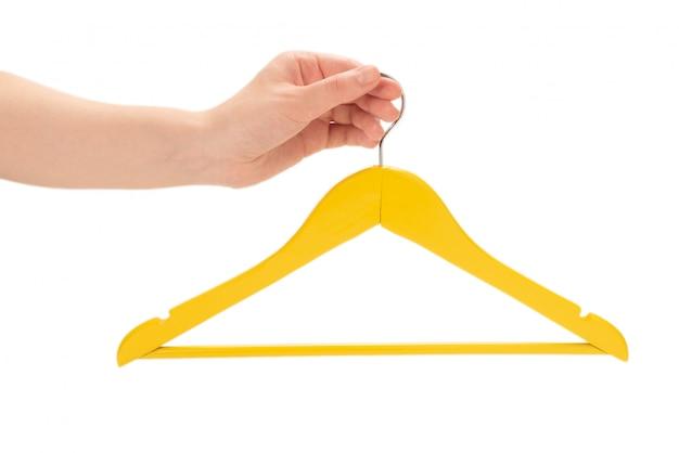 Cabide amarelo na mão da mulher isolado no branco