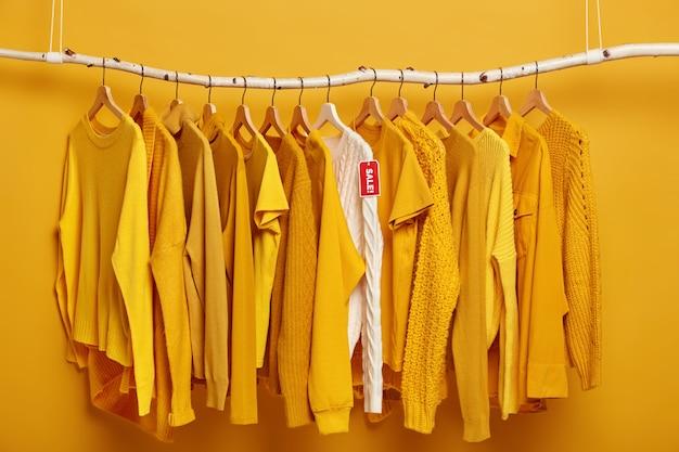 Cabide cheio de suéteres femininos amarelos sólidos. um suéter branco se destaca da coleção, em promoção.