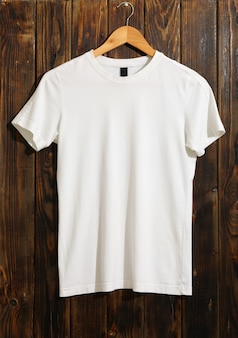 Cabide com camiseta branca em branco na madeira