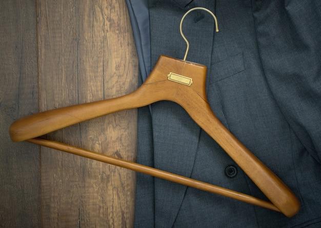 Cabide com o terno no conceito de madeira do negócio da loja da lavanderia da placa.