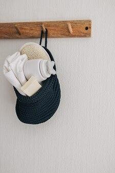 Cabide de gancho de madeira com produtos de beleza cosméticos para banheiro pendurado em uma cesta de corda de algodão feita à mão