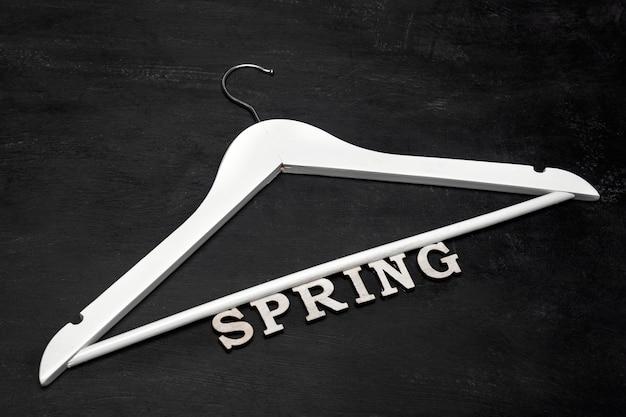 Cabide de madeira branca e inscrição primavera em fundo preto. coleção de roupas de primavera.