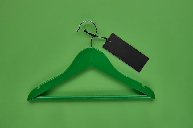 Cabide de madeira com etiqueta de papel preto isolada em fundo de papel verde. modelo de modelo sem emenda