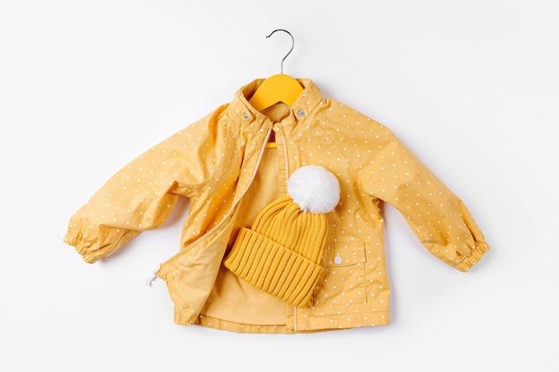 Cabide de suspensão de jaqueta amarela com chapéu em fundo branco. roupa de outono bonito de crianças.