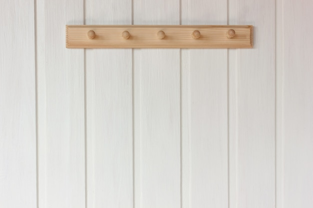 Cabide vazio de madeira natural em uma parede branca. interior rústico como pano de fundo, copie o espaço.