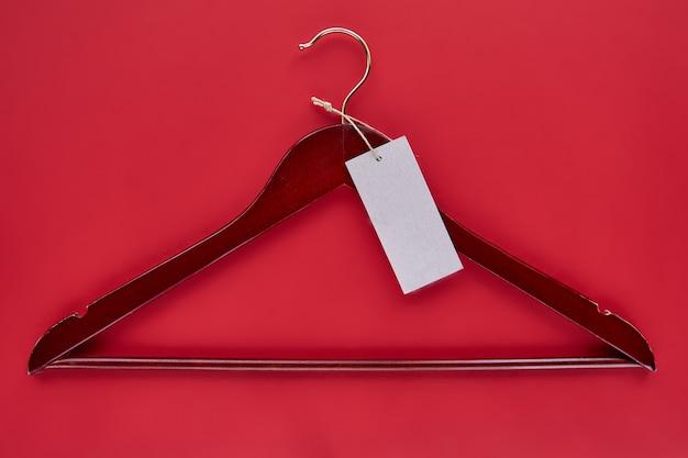 Cabide vermelho de madeira com etiqueta de papel preto isolada em fundo de papel vermelho. maquete de padrão sem emenda t