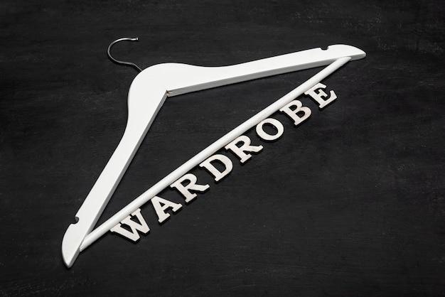 Cabides brancos e palavra de letras guarda-roupa na superfície preta