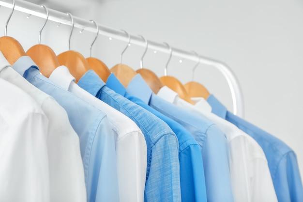 Cabides com camisas limpas na lavanderia, closeup