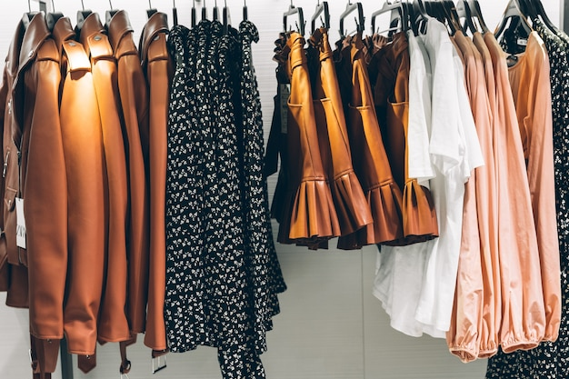 Cabides com diferentes roupas femininas em loja de moda