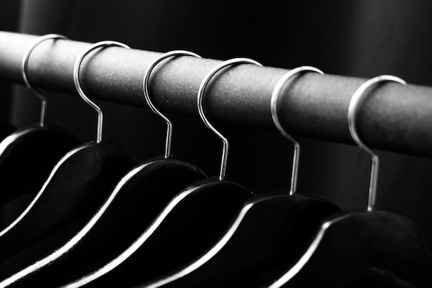 Cabides de contraste preto penduram no cabide de chão em um fundo escuro.