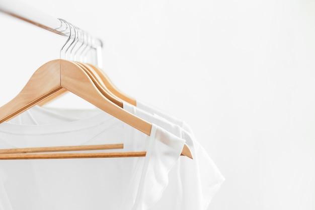 Cabides de madeira com roupas brancas femininas de verão