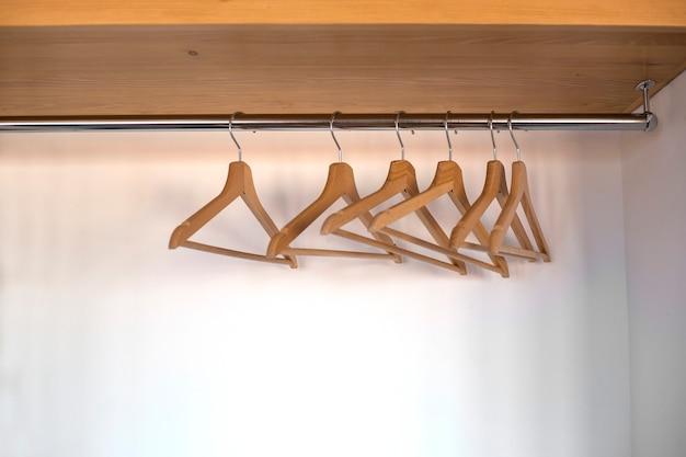 Cabides de madeira vazios pendurados em um armário em uma grade de metal