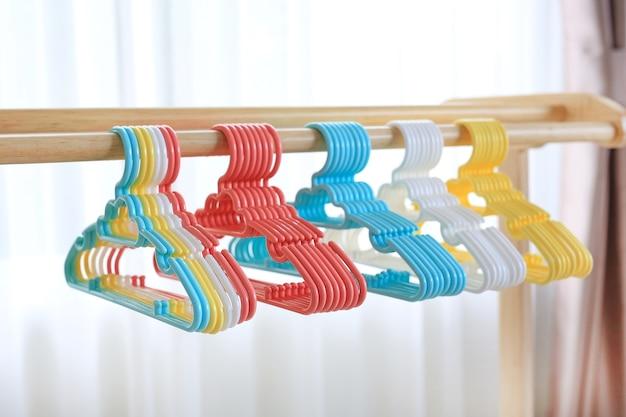 Cabides de plástico colorido no varal de madeira