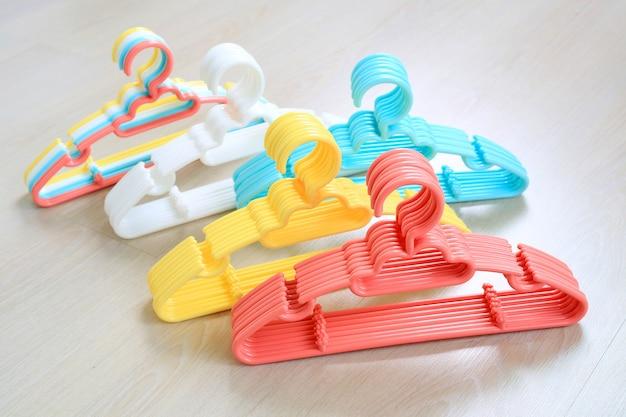 Cabides de plástico coloridos com fundo de madeira