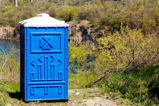 Cabine azul do bio toalete em um parque da montanha no dia de verão ensolarado.