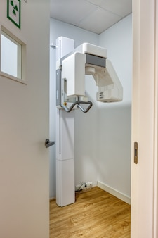 Cabine de raios-x na clínica odontológica moderna e atual, com paredes e portas brancas. vertical.