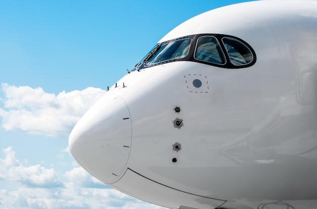 Cabine do nariz do avião de passageiros no céu azul de nuvens.