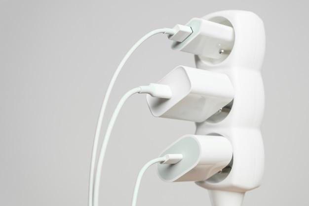 Cabo de extensão de escritório branco interno com três plugues de energia de vários tamanhos conectados a ele com espaço de cópia. carregadores de smartphones em réguas de energia para tomadas elétricas.