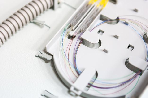 Cabo de fibra ótica do comunicate do trabalhador na caixa opto. instalando novo equipamento de rede