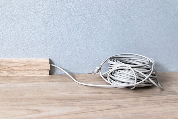 Cabo de internet rj 45 no rodapé ao longo da parede cinza da sala.