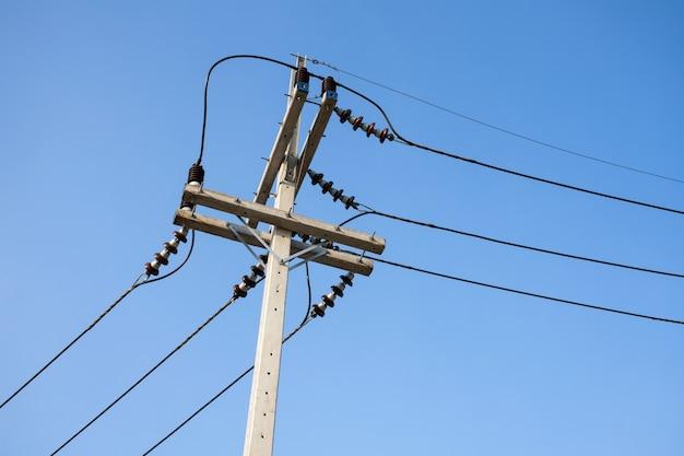 Cabos de alta tensão com isolador elétrico e equipamentos em poste elétrico de concreto.