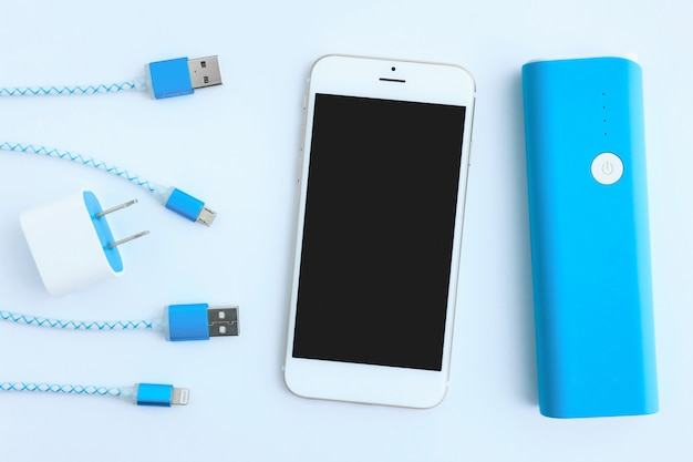 Cabos de carregamento usb com smartphone e banco de bateria na vista superior
