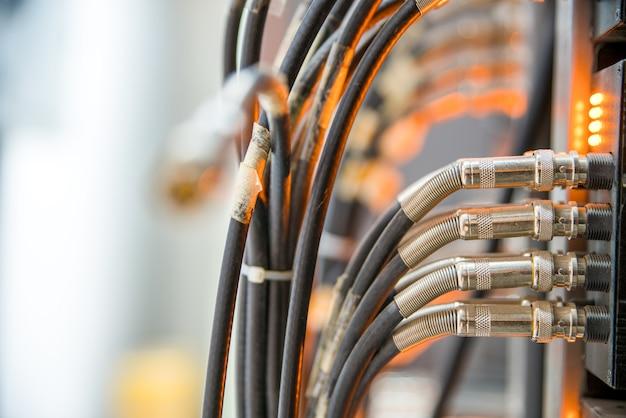 Cabos de rede conectados a um switch e painel de remendo, fundo de conceito de internet, símbolo de comunicações globais