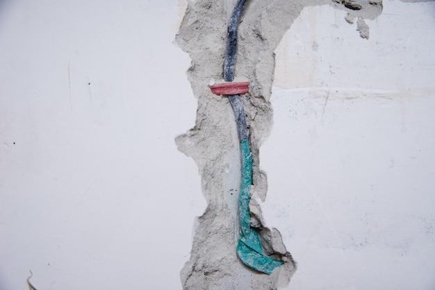 Cabos elétricos antigos em uma parede de tijolos. fiação de perigo