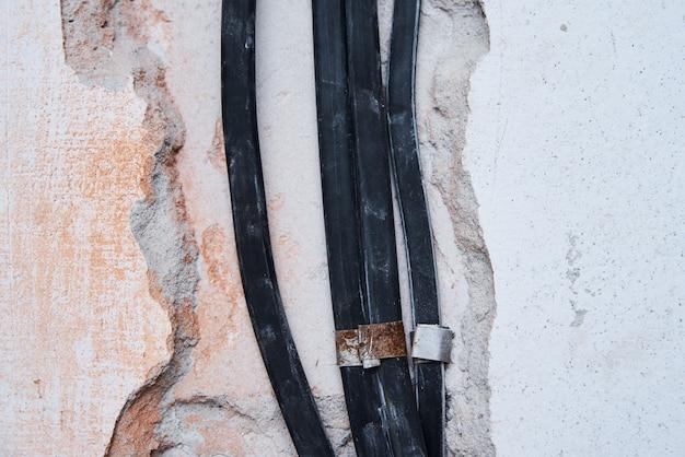 Cabos elétricos antigos em uma parede de tijolos.