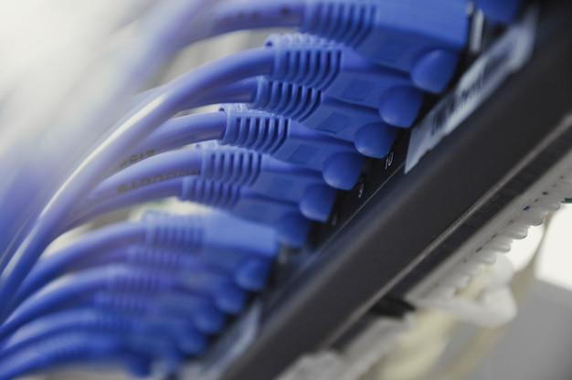 Cabos ethernet da telecomunicação conectados ao interruptor do internet, conceito do centro de dados.