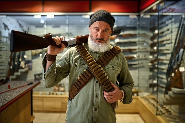 Caçador barbudo com rifle e bandoleiras na loja de armas. interior da loja de armas, variedade de munições e munições, escolha de armas de fogo, hobby de tiro e estilo de vida