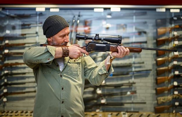 Caçador barbudo comprando rifle de caça com mira óptica na loja de armas. interior da loja de armas, sortimento de munições e munições, escolha de armas de fogo, passatempo de tiro