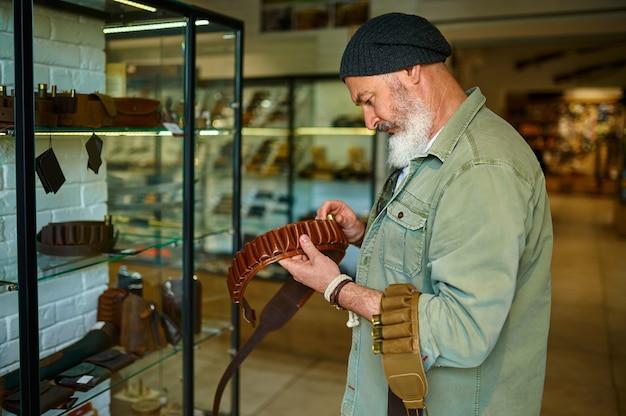 Caçador barbudo escolhendo bandoleira em loja de armas