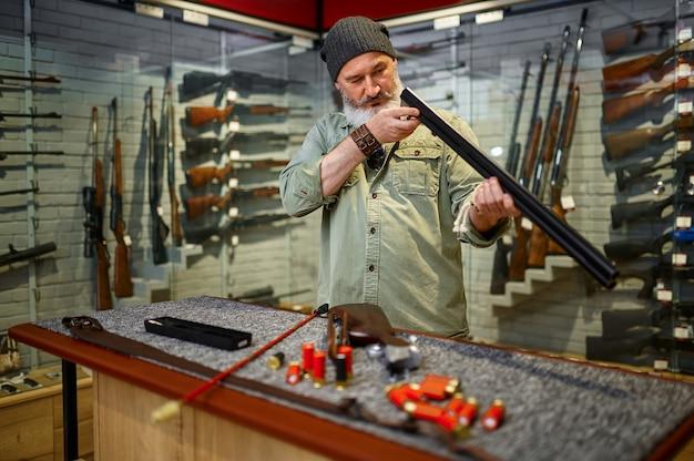 Caçador barbudo, limpando a vareta na loja de armas. interior da loja de armas, variedade de rifles e munições, escolha de armas de fogo, hobby de tiro