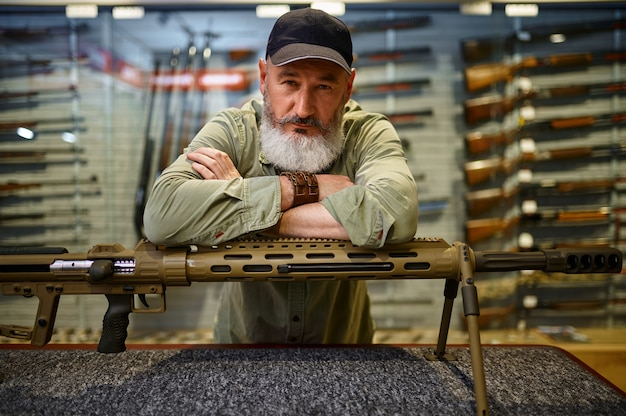 Caçador barbudo no balcão com um rifle poderoso na loja de armas. interior da loja de armas, variedade de munições e munições, escolha de armas de fogo, hobby de tiro e estilo de vida