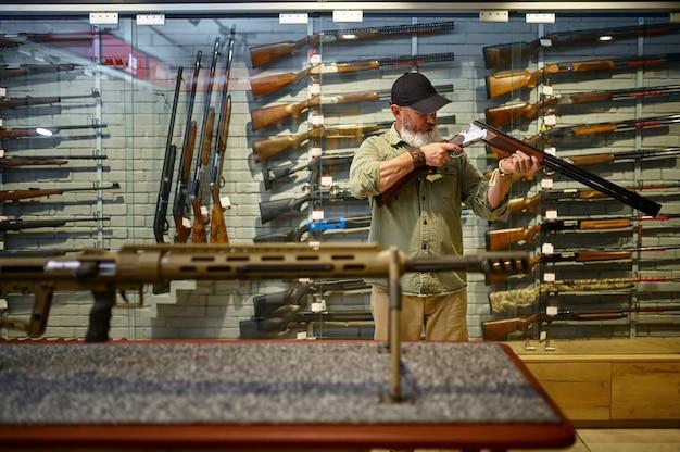 Caçador barbudo verifica o rifle de caça na loja de armas. interior da loja de armas, variedade de munições e munições, escolha de armas de fogo, hobby de tiro e estilo de vida