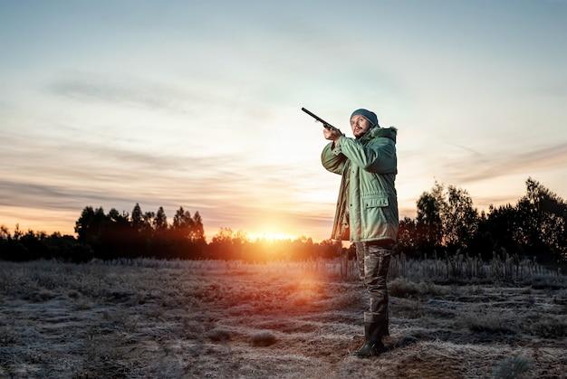 Caçador camuflado com uma arma durante a caça