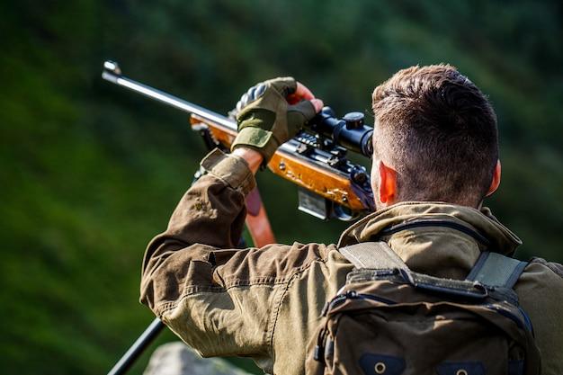 Caçador com arma de caça apontando