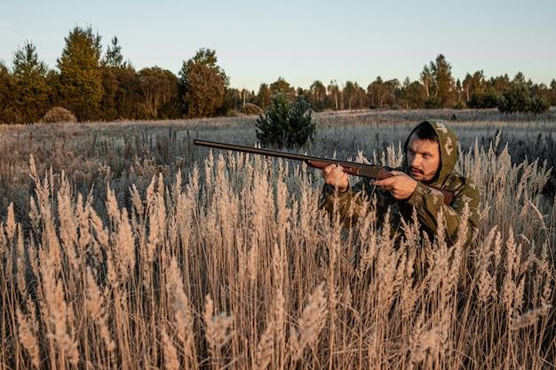 Caçador com uma arma está sentado na grama esperando por presas