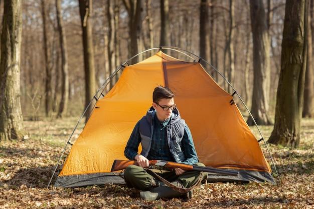Caçador com uma arma na floresta sentado perto da tenda