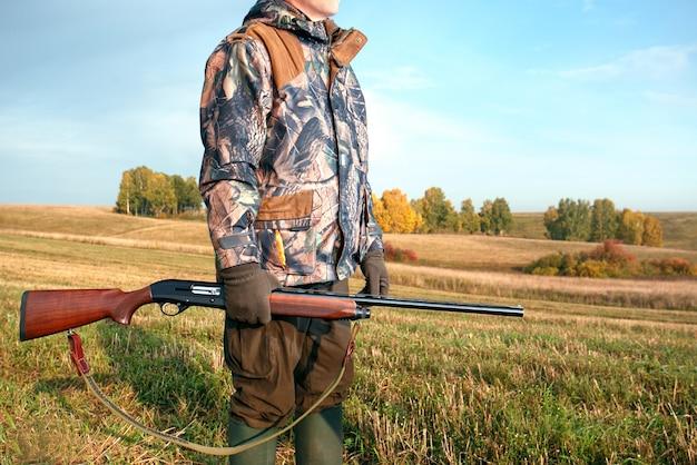 Caçador com uma arma no outono. caçador na temporada de caça ao outono.