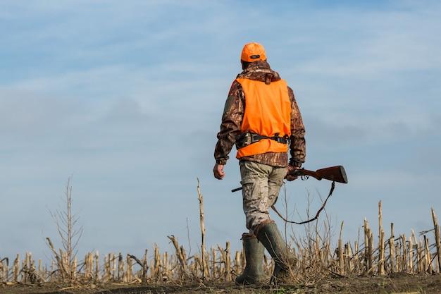 Caçador de patos com espingarda caminhando por um prado.