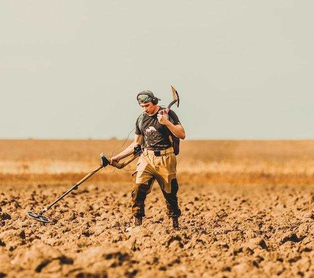Caçador de tesouros com detector de metais em um campo ao pôr do sol