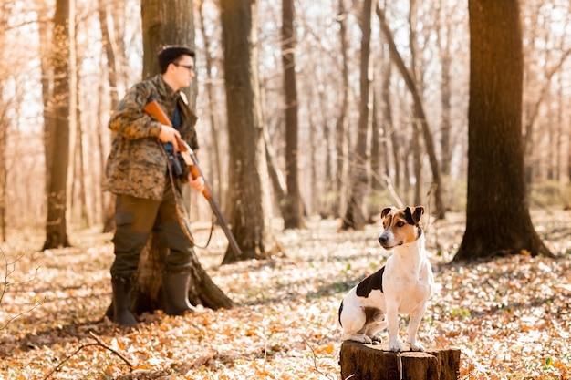 Caçador de yang com um cachorro na floresta