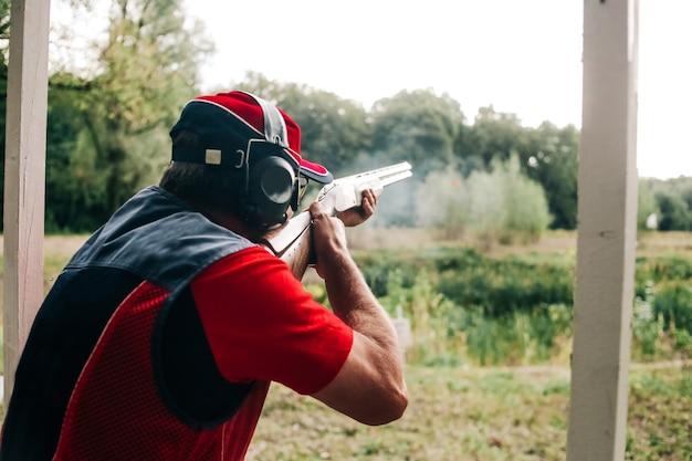 Caçador dispara com uma espingarda em um alvo em roupas especiais e fones de ouvido
