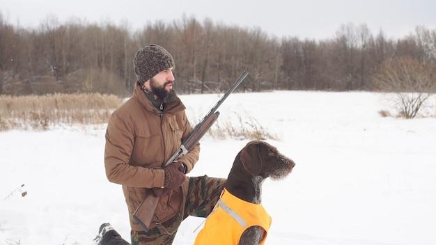 Caçador e seu cão estão esperando por suas presas em um campo, vista lateral