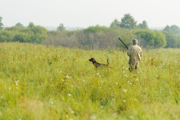 Caçador em roupas cáqui e boné com rifle e cachorro.