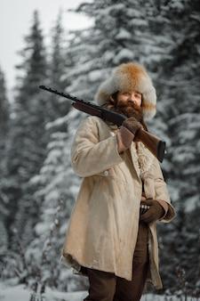 Caçador em roupas vintage com arma foge pela floresta